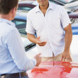 Man talking to car salesman - Stock Photo