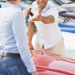 Royalty-Free Stock Photo: Man collecting new car from salesman