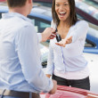 Woman collecting keys to new car — Stock Photo #4757775