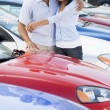 Young couple looking at new cars — Stock Photo