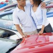Stock Photo: Young couple looking at new cars