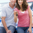 Young couple collecting new car - Stock Photo