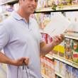 Young man grocery shopping - Stock Photo