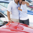 Young couple looking at new cars - Stock Photo