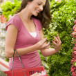 Stock Photo: Young womshopping for produce