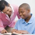 Elementary school teacher helping pupil — Stock Photo
