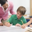 Elementary school teacher helping pupil — Stock Photo
