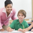 Foto Stock: Teacher and pupil in elementary school classroom