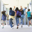 Elementary school pupils running outside - Stock Photo