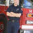 Portrait of a firefighter by a fire engine — Stock Photo #4758101