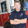 Photo: Portrait of a firefighter by a fire engine