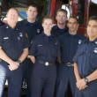 Portrait of firefighters standing by a fire engine — Stock Photo #4758111