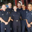 Photo: Portrait of firefighters standing by a fire engine