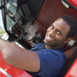 A firefighter sitting in the cab of a fire engine - Stock Photo