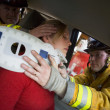 Firefighters helping an injured woman in a car — Stock Photo #4758180