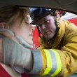 Firefighters helping an injured woman in a car — Stock Photo