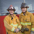 Stock Photo: Portrait of two firefighters by fire engine