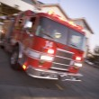 Fire engine rushing out of a fire station - Stockfoto