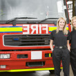 Portrait of two female firefighters standing by a fire engine — Stock Photo