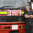 Portrait of a firefighter standing by a fire engine - Stock Photo