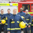 Stock Photo: Portrait of group of firefighters by fire engine