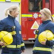 Two female firefighters by a fire engine - Stock Photo