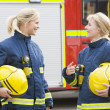 Stock Photo: Two female firefighters by a fire engine