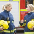 Two female firefighters by a fire engine — Stock Photo