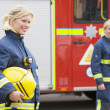 Two female firefighters by a fire engine — Stock Photo #4758266