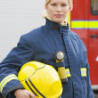 Royalty-Free Stock Photo: Portrait of a firefighter standing in front of a fire engine