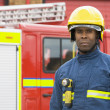 Portrait of a firefighter standing in front of a fire engine - Foto Stock