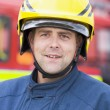 Portrait of a firefighter standing in front of a fire engine - Stock Photo