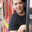 Stock Photo: Male firefighter sitting in cab of fire engine