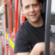 Male firefighter sitting in the cab of a fire engine - Stockfoto