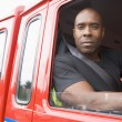 Male firefighter sitting in the cab of a fire engine — Stock Photo #4758307