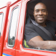 Photo: Male firefighter sitting in the cab of a fire engine