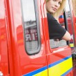 Female firefighter sitting in the cab of a fire engine — Stock Photo