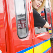 Female firefighter sitting in the cab of a fire engine - Stock Photo