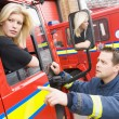 Firefighter sitting in the cab of a fire engine talking to a co- — Stock Photo