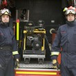 Firefighters standing by the equipment in a small fire engine - Stock Photo