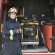 Firefighters standing by the equipment in a small fire engine — Stock Photo #4758347