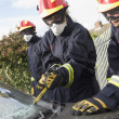 Firefighters breaking a car windscreen to help a car crash victi - ストック写真