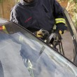 Firefighters breaking a car windscreen to help a car crash victi - Stock Photo
