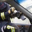 Firefighters breaking a car windscreen to help a car crash victi — Stock Photo