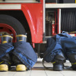 Firefighter's boots and trousers in a fire station - Stock Photo