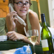 A young woman in her pyjamas on the phone and drinking wine — Stock Photo #4758397