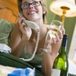 A young woman in her pyjamas on the phone and drinking wine - Stock Photo