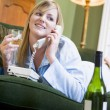 A young woman in her pyjamas on the phone and drinking wine — Stock Photo #4758399