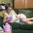 A young woman lying on her couch writing in her journal - Foto de Stock