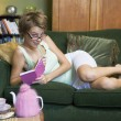 Stock Photo: A young woman lying on her couch writing in her journal